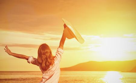 armonia: Mujer feliz de la belleza en el sombrero está de vuelta abrió las manos, se relaja y disfruta de la puesta de sol sobre el mar en la playa