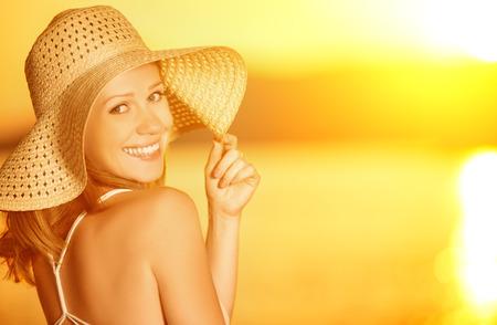 beleza feliz e sorridente mulher em um chapéu no mar ao pôr do sol na praia Imagens