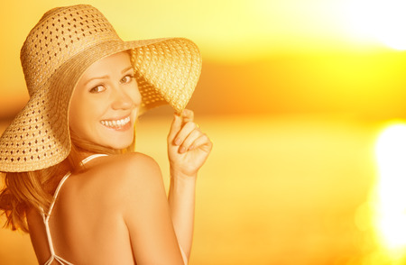 kapelusze: piękna szczęśliwa uśmiechnięta kobieta w kapeluszu na morzu o zachodzie słońca na plaży