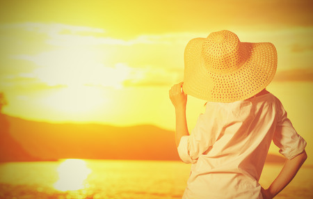 beach sunset: beauty happy woman in her hat is back and admire the sunset over the sea on the beach