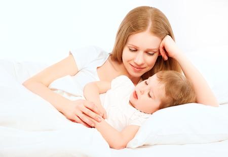 enfant qui dort: La mère de famille heureuse et bébé qui dort dans le lit
