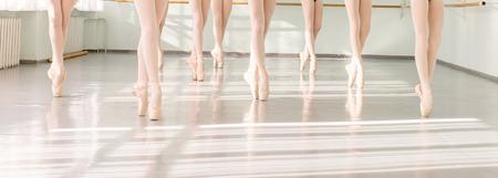 Nohy mladých tanečníků baletky ve třídě klasického tance, baletu