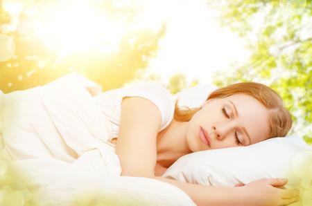 dormir: el concepto de descanso y relajación. Mujer durmiendo en la cama en el fondo de la naturaleza