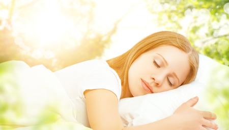 descansando: el concepto de descanso y relajación. Mujer durmiendo en la cama en el fondo de la naturaleza