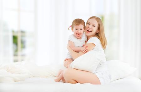 De gelukkige familie moeder en baby dochter spelen en lachende baby kussen in bed
