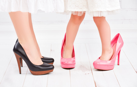 mother and children: piernas madre y su hija peque�a fashionista ni�a en zapatos de color rosa en tacones altos