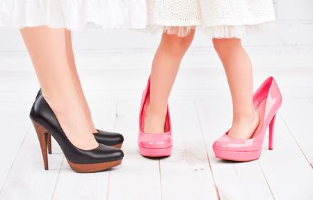 tacones rojos: piernas madre y su hija pequeña fashionista niña en zapatos de color rosa en tacones altos