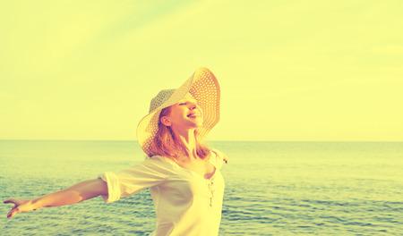 帽子のハッピー ビューティー女性彼の手を開く、リラックスし、ビーチの海に沈む夕日を楽しむ