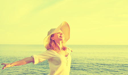 hand free: Happy beauty woman in a hat opened his hands, relaxes and enjoys the sunset over the sea on the beach