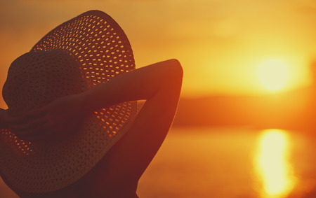 beauty happy woman in her hat is back and admire the sunset over the sea on the beach