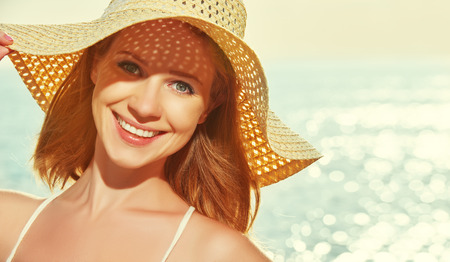 beauty happy smiling woman in  hat enjoy sea at sunset on the beach