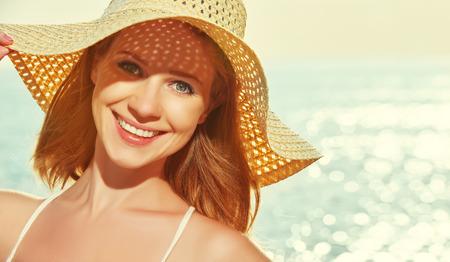 kapelusze: piękna szczęśliwa uśmiechnięta kobieta w kapeluszu cieszyć morze o zachodzie słońca na plaży