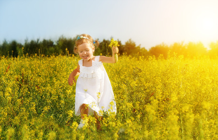 happy little child girl in a white dress running on field with a bouquet of yellow flowers, wildflowers
