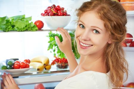 nevera: Mujer feliz de pie en el refrigerador abierto con frutas, verduras y alimentos saludables Foto de archivo