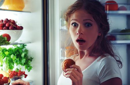 personas comiendo: mujer come dulces en la noche para colarse en un refrigerador Foto de archivo