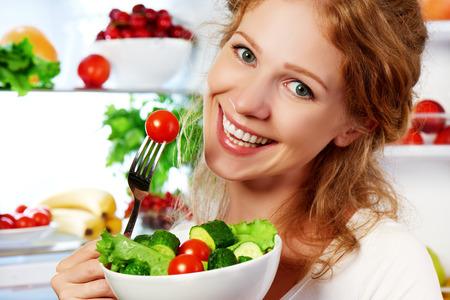 happy woman eats healthy food vegetable vegetarian salad about refrigerator Archivio Fotografico
