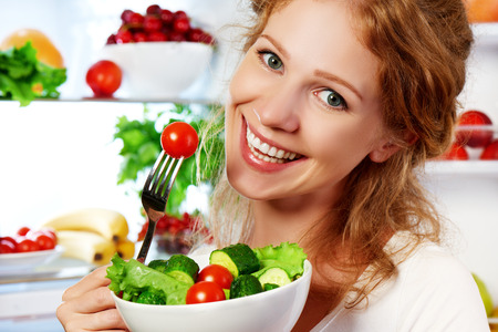 refrigerator with food: happy woman eats healthy food vegetable vegetarian salad about refrigerator Stock Photo