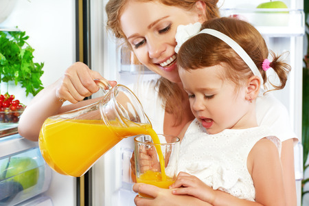 happy family mother and baby daughter drinking orange juice in the kitchen near the refrigerator Standard-Bild