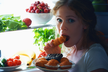 eating pastry: woman eats sweets at night to sneak in a refrigerator