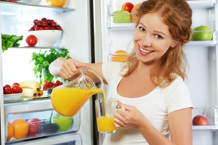 juice glass: happy woman eating healthy food, drinking orange juice about refrigerator Stock Photo