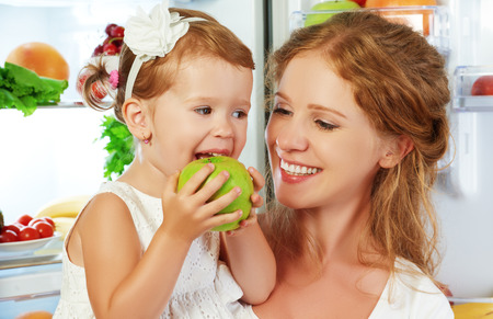 refrigerator with food: happy family mother and child baby daughter around the refrigerator with healthy food fruits and vegetables Stock Photo