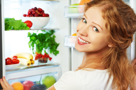 red kitchen: Happy woman standing at the open refrigerator with fruits, vegetables and healthy food