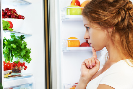 woman eating fruit: Happy woman standing at the open refrigerator with fruits, vegetables and healthy food