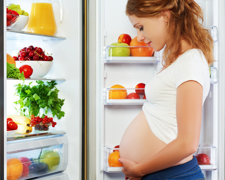 pregnant mom: nutrition and diet during pregnancy. Pregnant woman standing near refrigerator with fruits and vegetables