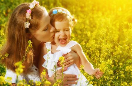 beso: familia feliz en el prado de verano, madre besando ni�a peque�a hija con flores amarillas