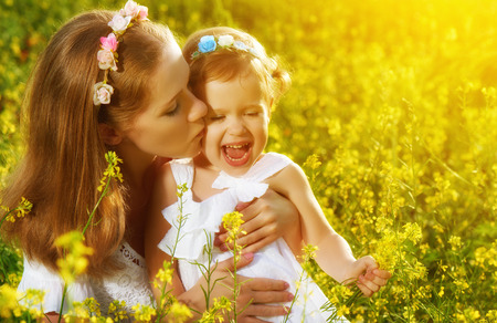 women kissing women: happy family in the summer meadow, mother kissing little daughter girl child with yellow flowers Stock Photo