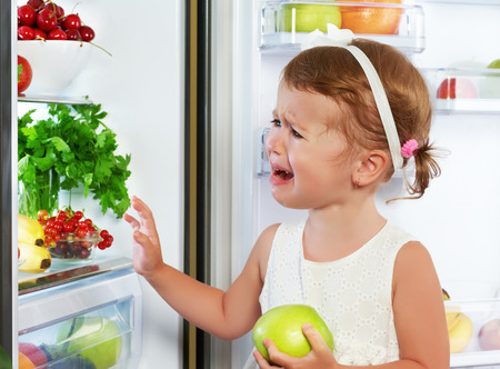 little girl child is crying and acting about fridge with healthy eating fruit