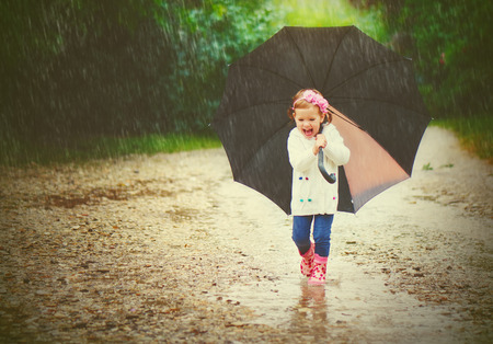 happy baby girl with an umbrella in the rain runs through the puddles