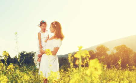 family playing: happy family, mother and little daughter girl child in the summer meadow with yellow flowers