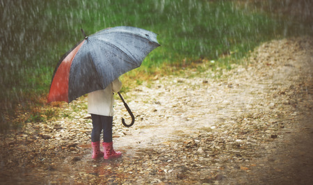 water fall: happy baby girl with an umbrella in the rain runs through the puddles