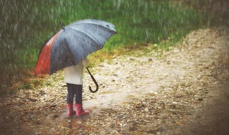 lluvia paraguas: niña feliz con un paraguas bajo la lluvia corre por los charcos Foto de archivo