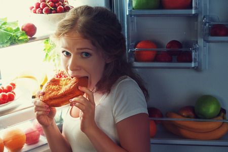 woman eats sweets at night to sneak in a refrigerator