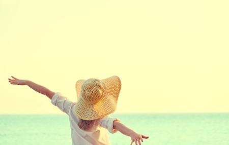 모자에 행복 아름다움 여자는 다시 이완, 그의 손을 열고 해변에서 바다 일몰을 감상 할 수 있습니다