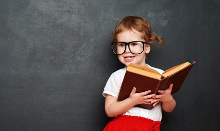 colegiala: colegiala feliz niña con un libro de la pizarra