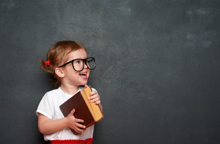 幸せな小さな女の子女子高生黒板から本 写真素材