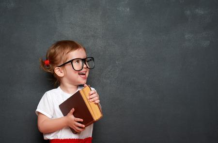 pizarron: colegiala feliz niña con un libro de la pizarra