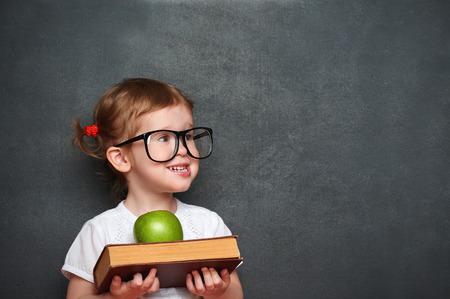 かわいい女の子の女子高生の本と林檎、学校の理事会