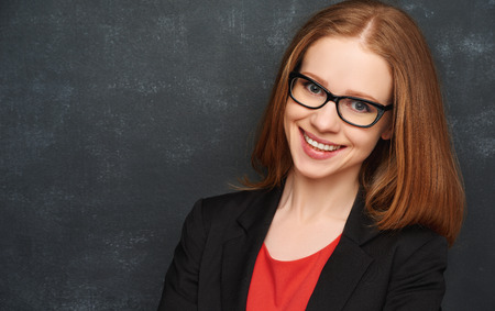 female: happy business woman with glasses in red from the  blank blackboard