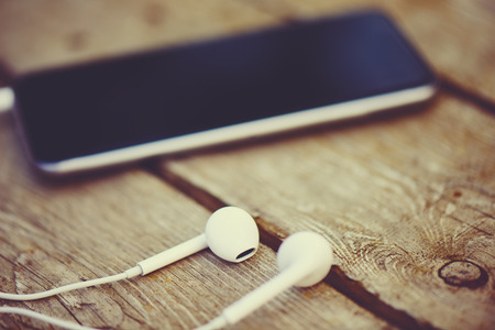 office accessories: cell phone and headphones lay on an old wooden table Stock Photo