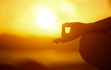 mente: Concepto de yoga. mano de la mujer la práctica de loto en la playa al atardecer Foto de archivo