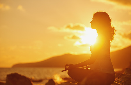 Pregnant woman practicing yoga, sitting in lotus position on a beach at sunset