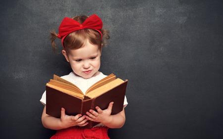 colegiala: colegiala ni�a feliz divertida con un libro de la pizarra