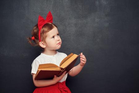 Lustig glückliches kleines Mädchen Schulmädchen mit einem Buch aus der Tafel Standard-Bild - 42043236