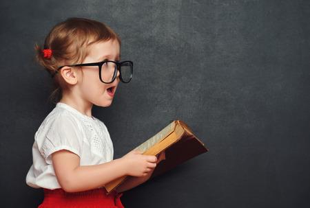 grappig gelukkig meisje schoolmeisje met een boek uit de blackboard