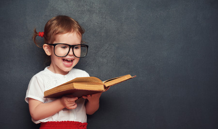 young: funny happy little girl schoolgirl with a book from the blackboard