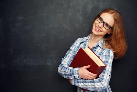 portrét: šťastná dívka student s brýlemi a kniha z tabule Reklamní fotografie